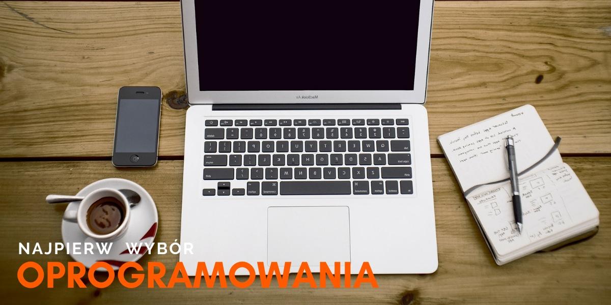 Leżący na stole laptop, notes, telefon oraz kawa